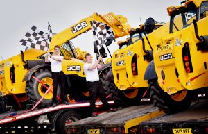 A FLEET of JCB machines is under starterÕs orders to take on a starring role at the British Grand Prix.  Fourteen JCB Loadall telescopic handers left the JCB World HQ in Rocester, Staffordshire, this morning on trucks bound for Silverstone in Northampton ahead of the Formula 1 Grand Prix next weekend.  The 531-70 models - which can lift weights of three tonnes - will provide four days of support at the race circuit. Today they were sent on their way in colourful racing style with the convoy of trucks led by a JCB 3CX Compact backhoe loader wrapped in the colours of Williams Martini Racing to mark JCBÕs partnership with the British-based F1 team.  Sam Goodman, 21, of Derby (left) Loadall Development Engineer George Cooper, 25, of Tean, near Cheadle and , who works in product sales at JCBÕs World HQ, wave off the fleet of machines with traditional racing chequered flags.